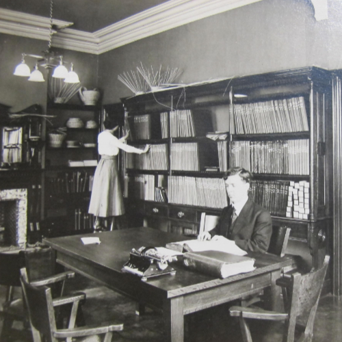 Dr. Carruthers sits at the table reading braille with another braille book beside him and a mechanical brailler opposite. Miss Mitchell is standing on a stool tidying or sorting books on the shelves. The room is lined with book shelves and there are unfinished basket weaving projects on the top of the bookcases.