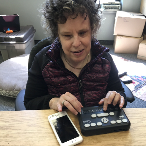 Kim Kilpatrick sits at a table with her hands on an Orbit brailler and a smart phone in front of her.