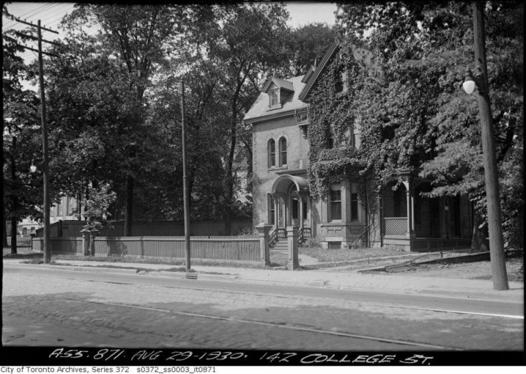 Large residential building with fence in front and driveway at right hand side, surrounded by trees and with ivy growing up a portion of the frontage.
