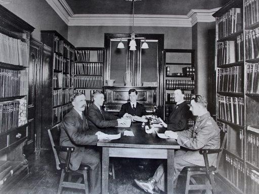 Cinq hommes, dont un en uniforme, sont assis autour d'une table dans la bibliothèque, les mains sur des pages braille. Dr Carruthers a une machine à écrire braille devant lui.