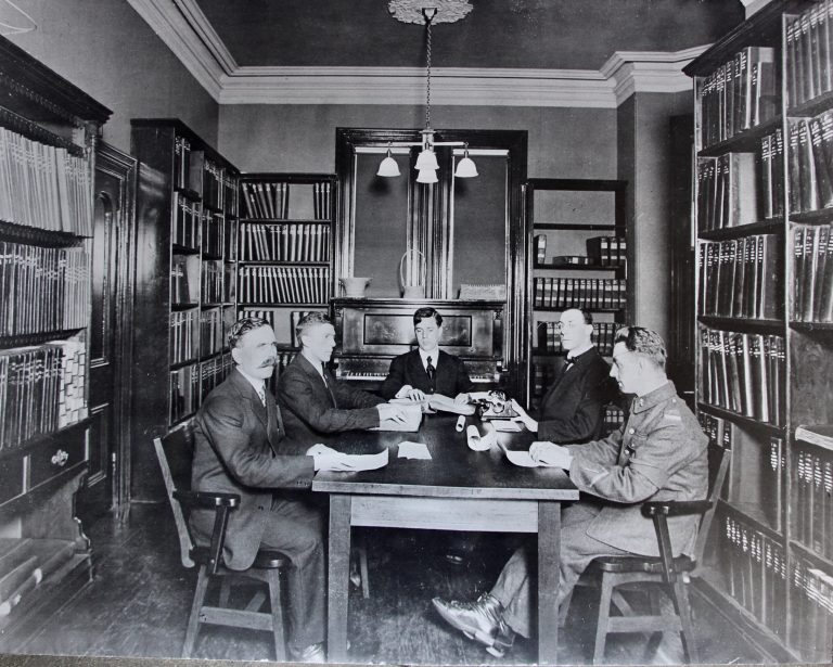 Five men, one in uniform, are seated around a table in the library with their hands on pages of braille. Dr. Carruthers has braille typewriter in front of him