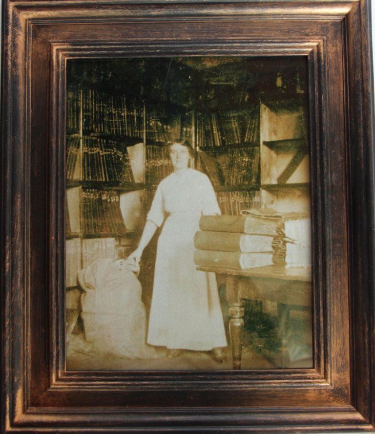 Woman stands between a waist high canvas mailing bag and a pile of three bulky braille books on the table. Shelves containing books line the room she is working in. Photograph is framed in dark wood