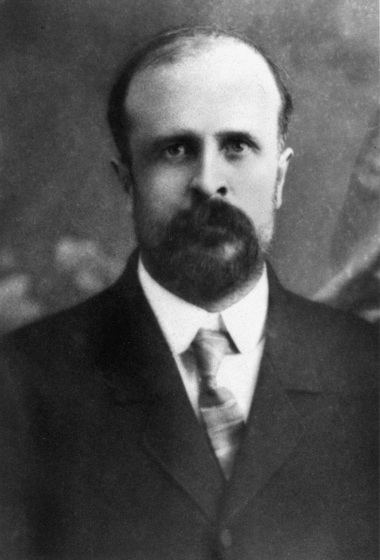 Portrait de Bert Robinson – un homme barbu vêtu d'un costume et d'une cravate