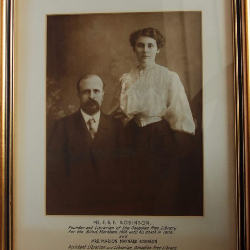 Mr. Robinson is seated with Mrs. Robinson standing on his left with her hand behind his shoulder. He is bearded and wearing a suit and tie, she is in white lacy blouse with voluminous sleeves and a long, dark skirt