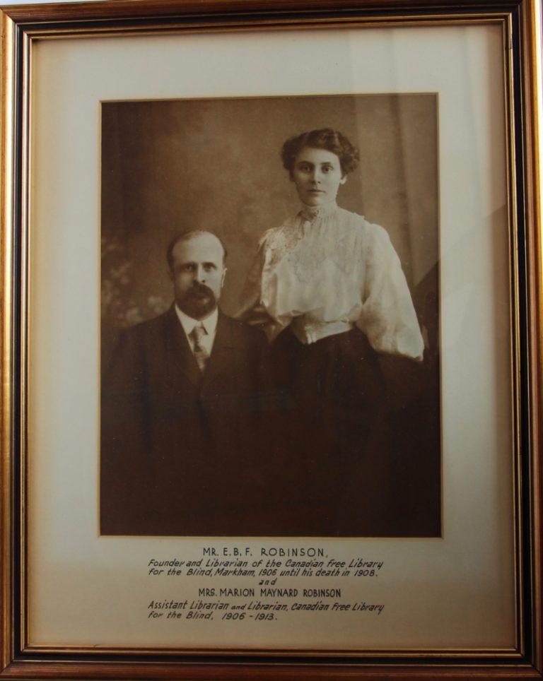 M. Robinson est assis à côté de Mme Robinson, qui est debout, à sa gauche, sa main derrière son épaule. Il est barbu et porte un costume et une cravate, elle est en blouse de dentelle blanche avec des manches volumineuses et une longue jupe noire.