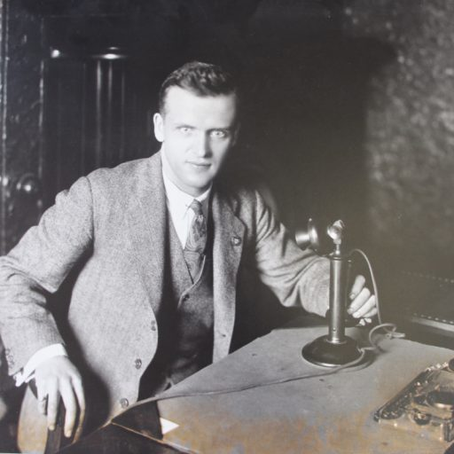 Baker, wearing suit and tie, is sitting at a desk, right hand on the arm of the chair, left hand on the stem of an upright telephone. Dictaphone equipment on the desk is for transmitting informtion to the field officers