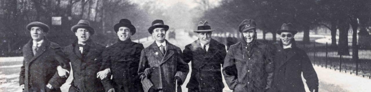 Sept hommes munis de cannes marchant en parallèle bras dessus bras dessous vers l'appareil photo sur une rue enneigée de Regent's Park.