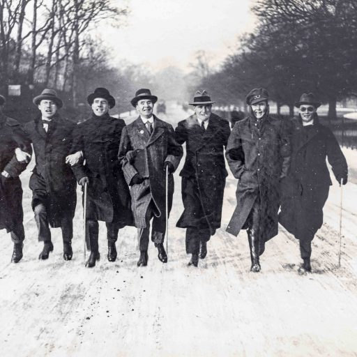 Seven men in a row with linked arms and carrying canes are running towards the camera on a snowy road. All the men are wearing hats and heavy greatcoats