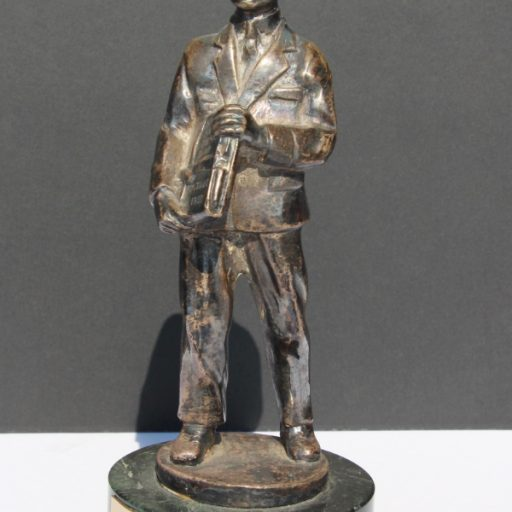 """Statue with marble plinth and metal postman figure. """"Figure is holding a bound book inscribed with Books for the Blind, Postage Free."""""""