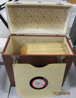 An open box with hinged lid and carrying handle, containing the disks with one disk leaning against the box to show the label - Talking Book ....