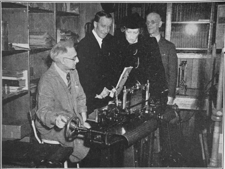 A man sits at braille production equipment with Lord and Lady Tweedsmuir looking on. Sherman Swift stands behind the group