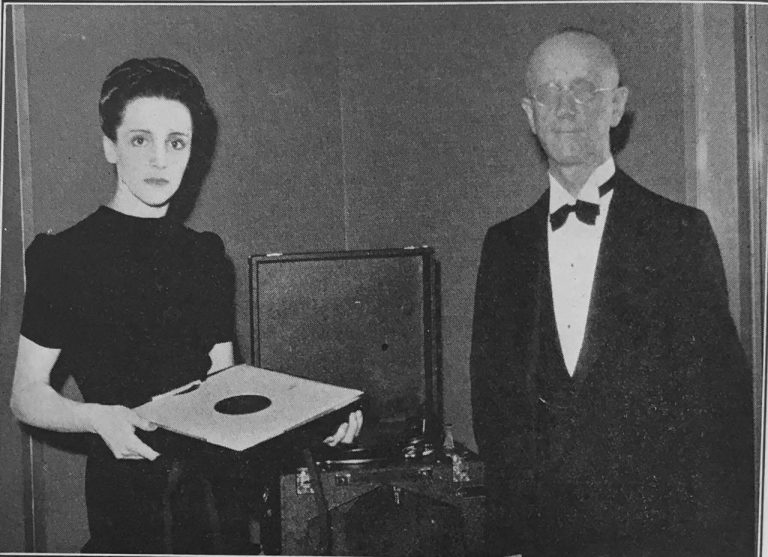 On the left Mlle. Curie is holding a box of phonograph disks, centre is an open phonograph machine, Dr. Swift stands on the right