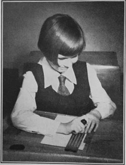 The young girl is wearing school uniform, shirt, tie and tunic, sitting at table