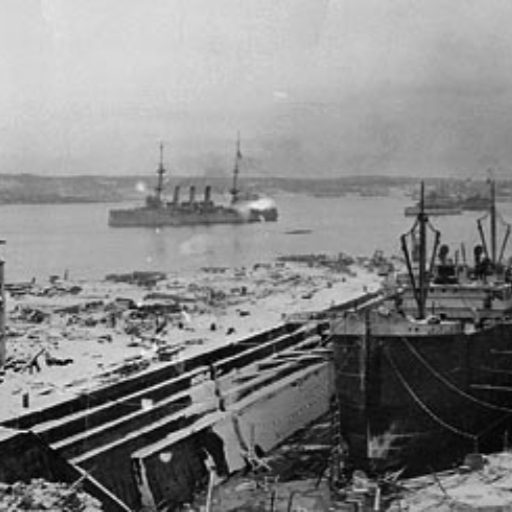View of Halifax Harbour showing military ships in the harbour and destruction of buildings and ship in drydock in the foreground. The ground is covered with snow
