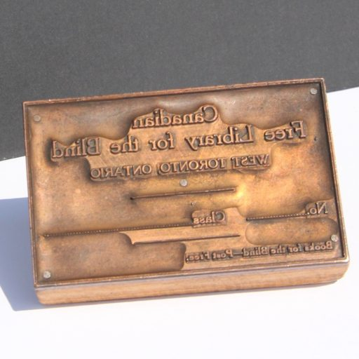 Reverse text on a brass plate nailed to a wooden block