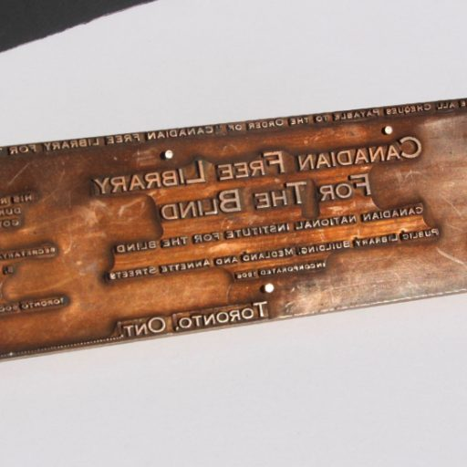 Brass plate with reverse text nailed to a wooden block