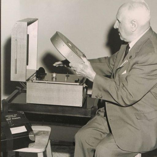 Un homme est assis à la table avec une cassette dans sa main gauche, tandis que sa main droite sent le haut de la machine pour trouver le bon placement pour jouer le livre parlé.