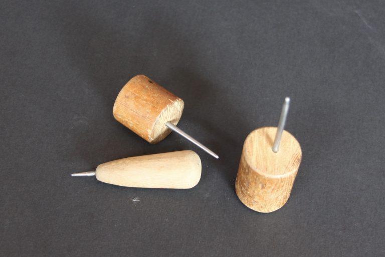Trois stylets avec des poignées en bois : deux sont placés sur leurs côtés et un est vertical sur sa poignée en bois