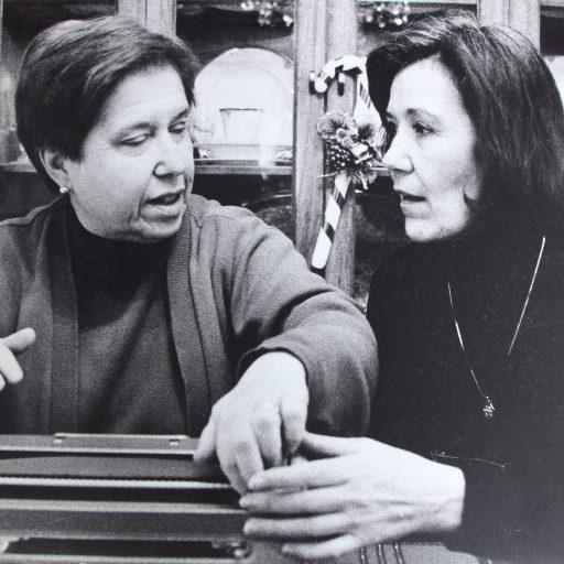 Deux femmes sont assises à une table devant une machine braille. L'étudiante a sa main au-dessus de la machine et l'enseignante guide sa main.