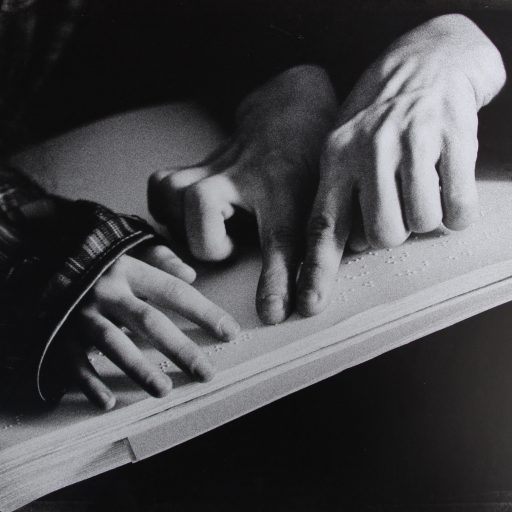 A student's hands are on a page of braille with another hand guiding the progress
