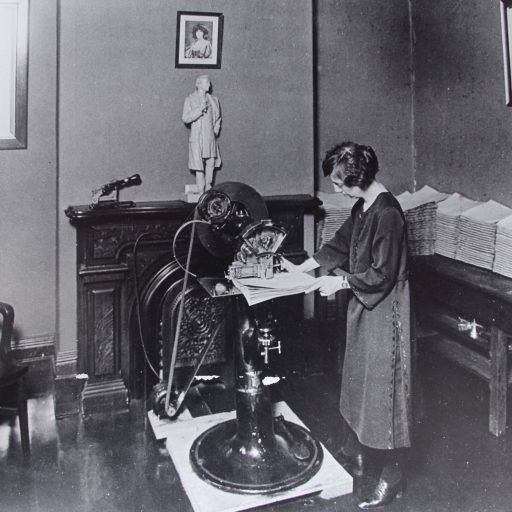 Woman stands in front of a waist high stitching machine feeding a document through the stitcher. Behind her on a table are stacks of completed documents