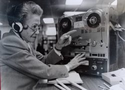 A woman, wearing headphones, is pointing at the reader and has her hand on the start button for recording. The book that is being recorded lies open on the table in front of her