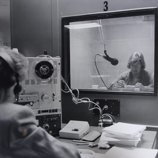 A woman is sitting in the closed studio booth reading into the microphone while the monitor watches through a glass windo and listens with headphones on her head. The reel to reel recording equipment is on the monitor's left hand side