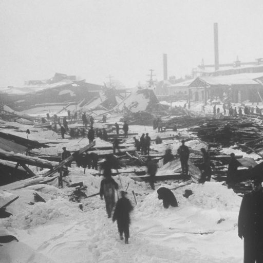 Heavy snow covers the ground and ruins of buildings