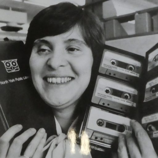 Young woman is holding one open and one closed container of cassette tapes up beside her head. The talking books are the property of North York Public Library