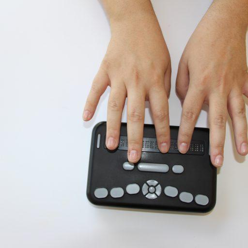 Vue du haut du lecteur avec deux mains sur les touches braille
