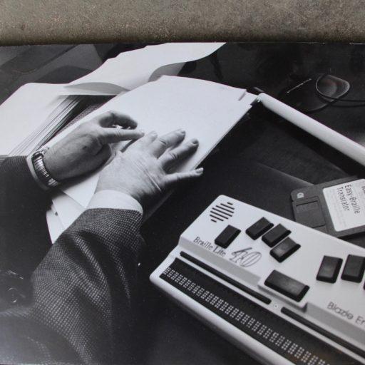 Deux mains utilisées pour lire le braille sur papier avec le Braille Lite à droite. Une disquette intitulée Easy Braille Translator (traducteur de braille facile) se trouve sur la table à côté de l'équipement.