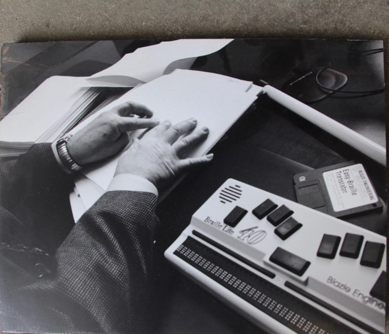 Two hands reading braille on paper with the Braille Lite to the right. A diskette entitled Easy Braille Translator is on the table beside the equipment