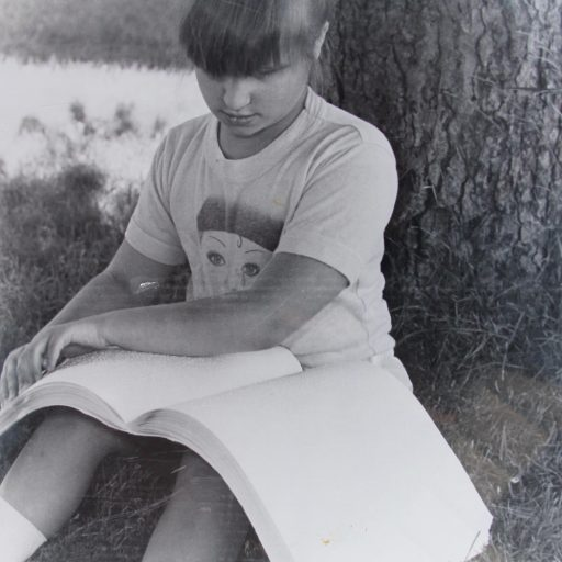 Young girl sitting under a tree reading from a large braille book on her lap