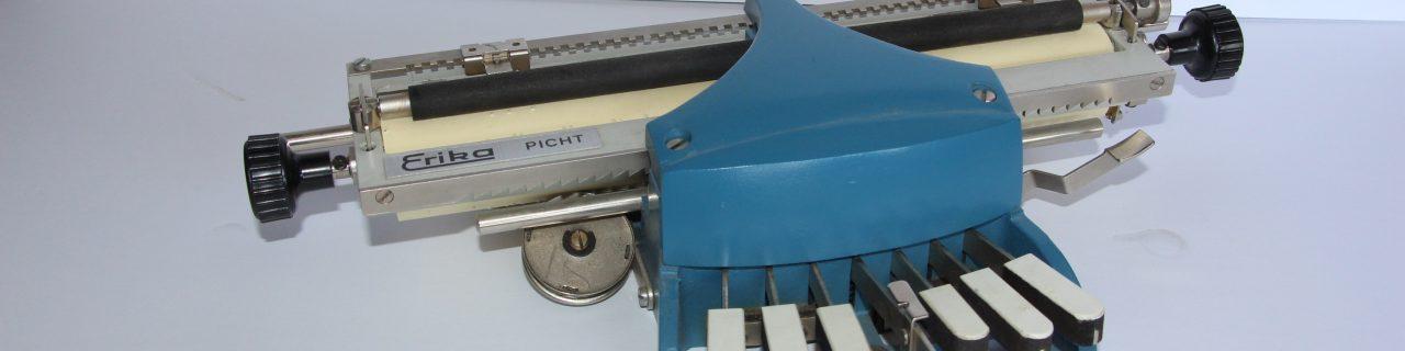 Le modèle portatif de la machine braille est bleu et il comprend des touches en bois recouverts de faux ivoire blanc