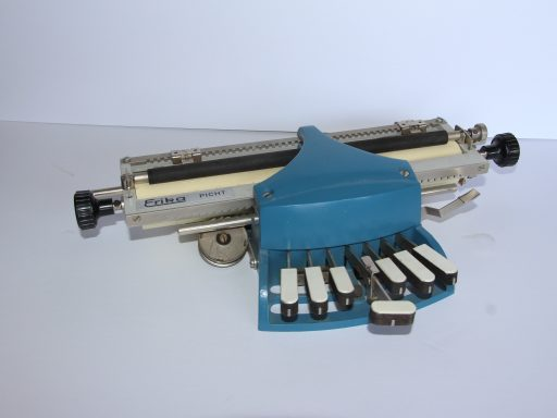 Portable model of the brailler is painted blue and has wood keys covered with white simulated ivory
