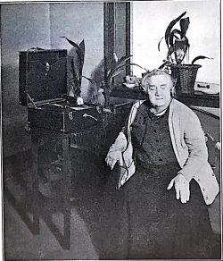Woman wearing headphones listening to a phonograph disk on playerFemme munie de casquesécoutant un disque de phonographe