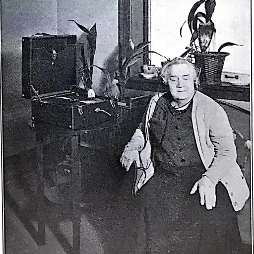 Woman wearing headphones listening to a phonograph disk on playerFemme munie de casquesécoutant un disque de phonographe