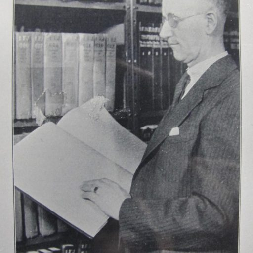 Mr. Swift is reading braille with his left hand standing beside one of the library stacks of braille books