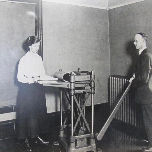 Miss Swift is feeding paper into the press, S. Swift stands to the right of the machine pressing down on a lever which presses the braille embossed plate into the paper