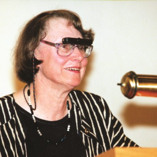 Frances Cutler, ancienne présidente, Conseil d'administration national d'INCA, porte des télescopes attachés à ses lunettes afin de voir la réaction du public pendant qu'elle parle sur le podium.