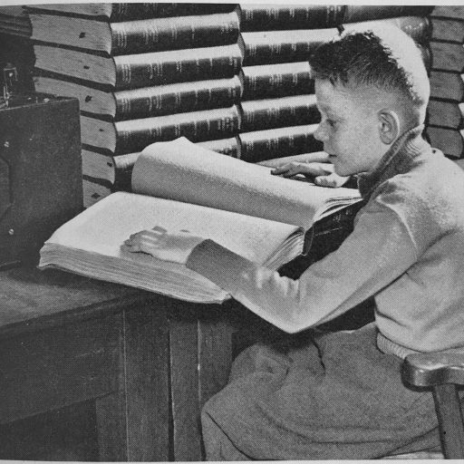 Young boy reading a large braille book with his left hand seated at a table, surrounded but stacks of other books