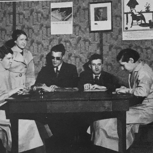 Four people sitting at a table with their hands on braille sheets with the teacher standing behind them