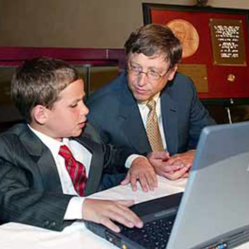 Timothy has his hands on the keyboard of a laptop and Bill Gates is leaning over listening intently to Timothy