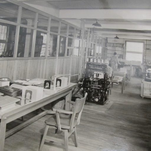 A long narrow room containing a table with finished products on it, a man sitting at a press and a woman with her back to the camera working at the end of the room