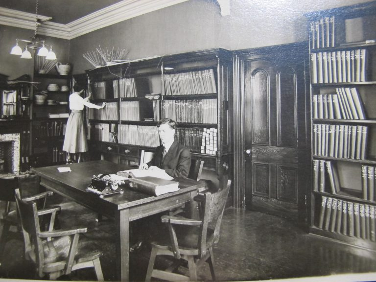 Dr, Carruthers sits at the table reading braille with another braille book beside him and a mechanical brailler opposite. Miss Mitchell is standing on a stool tidying or sorting books on the shelves. The room is lined with book shelves and there are unfinished basket weaving projects on the top of the bookcases