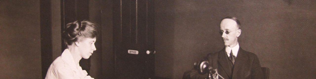 Son assistante écrit la dictée avec un stylo, M. Swift est assis de l'autre côté du bureau et un téléphone est entre eux sur le bureau.