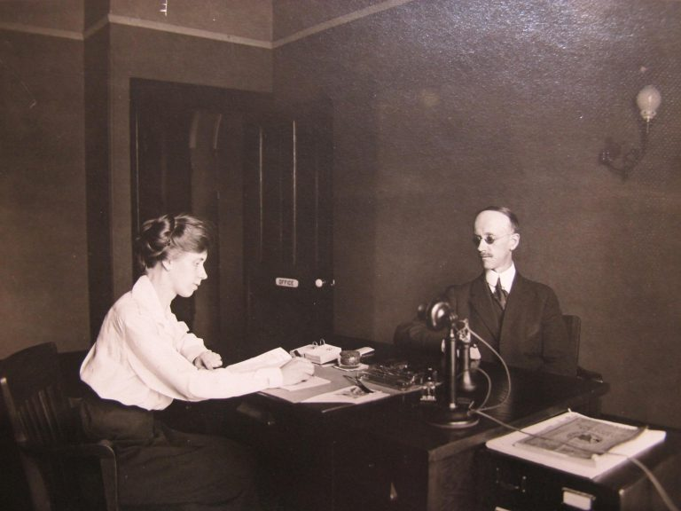 His assistant is taking dictation with a pen, Mr. Swift sits on the othe side of the desk with a telephone on the desk between them