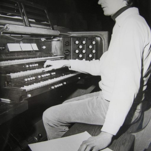 Young man sits at two level keyboard of an organ with his right hand on the upper keyboard and his left hand on the braille music beside him on his stool