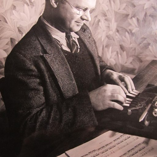 Man sitting at a desk with printed music open on his left hand side.