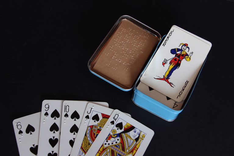 Braille playing cards - closeup of 6,9,10, jack and queen of spades with braille in top left corner, an open tin with braille instructions inside the lid and the joker on top of the pack